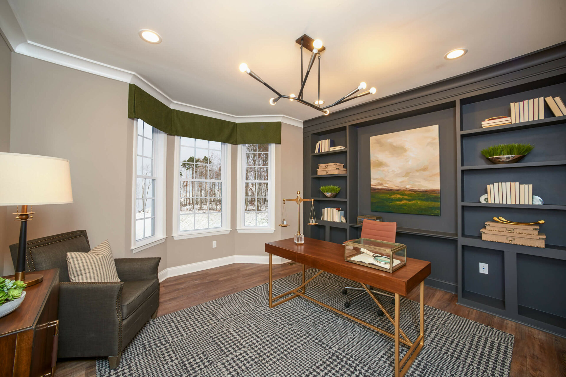 The office or den is smartly finished with a wall of richly-colored custom built-ins for books and more in the Hancock Model